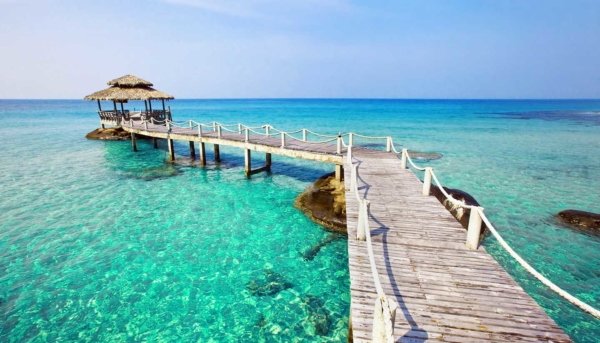 Pier and gazebo on clear blue water at a tropical beach